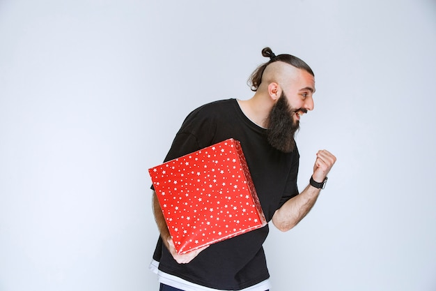 Homem com barba segurando sua caixa vermelha de presente, curtindo e se sentindo feliz.