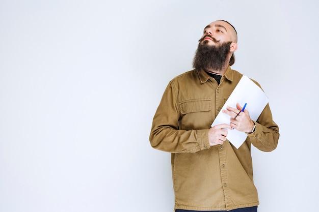 Homem com barba, segurando sua lista de relatórios e esperando com confiança.
