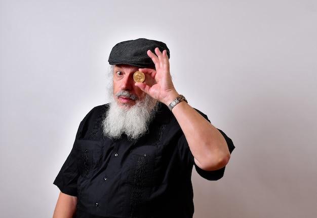 Homem com barba segurando um bitcoin e olhando para ele