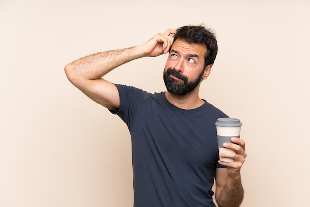 Homem com barba segurando um café com dúvidas e com expressão de rosto confuso