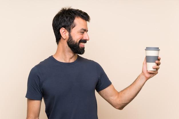 Homem com barba segurando um café com expressão feliz