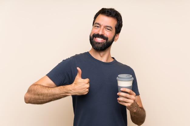 Homem com barba segurando um café com polegares para cima porque algo bom aconteceu
