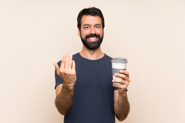 Homem com barba segurando um café convidando para vir com a mão. feliz que você veio