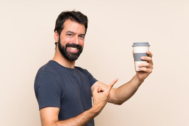 Homem com barba segurando um café e apontando-o