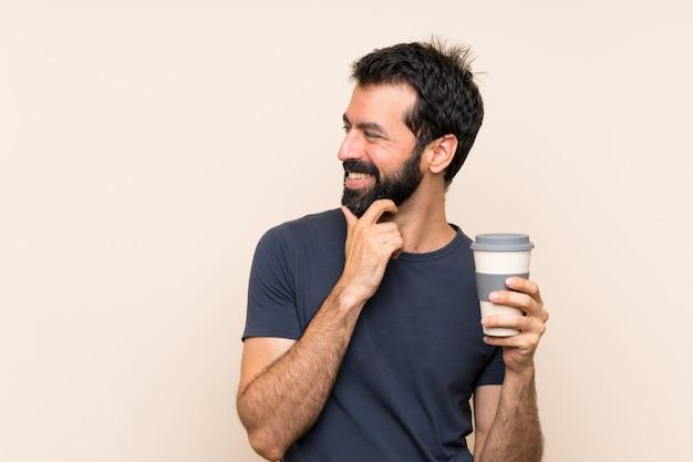 Homem com barba segurando um café pensando uma idéia