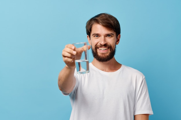 Homem com barba segurando um copo de água na mão na visão recortada do modelo de camiseta branca azul.