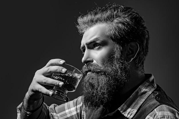 Homem com barba segurando um copo de conhaque