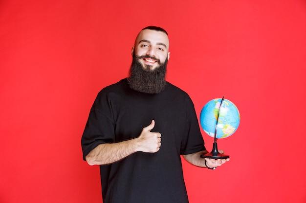 Homem com barba segurando um globo do mundo e gostando.