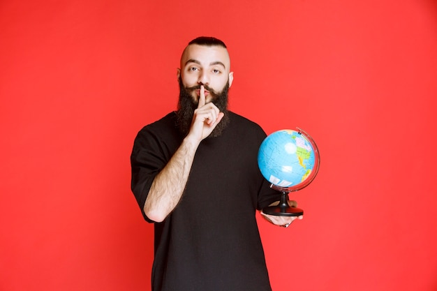 Homem com barba segurando um globo do mundo e pedindo silêncio.