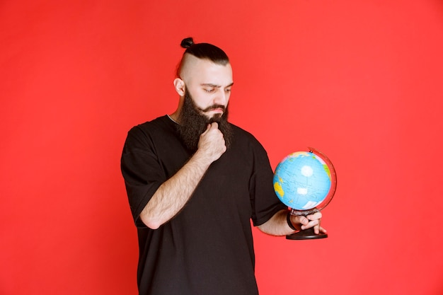 Homem com barba segurando um globo do mundo e procurando lugares sobre ele.