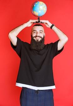 Homem com barba segurando um globo do mundo.