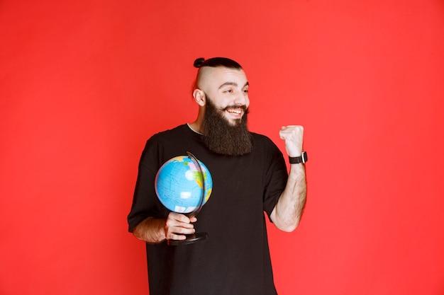 Homem com barba segurando um globo e mostrando o punho.