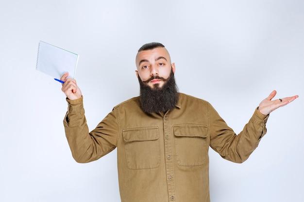 Homem com barba segurando um papel de teste e parece confuso e pensativo.