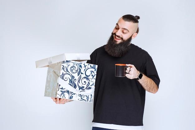 Homem com barba segurando uma caixa de presente azul aberta com uma xícara de café e parece feliz.