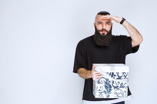 Homem com barba segurando uma caixa de presente azul branca e parece desapontado.