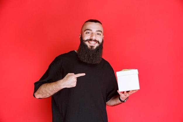 Homem com barba segurando uma caixa de presente branca e apontando para ela.