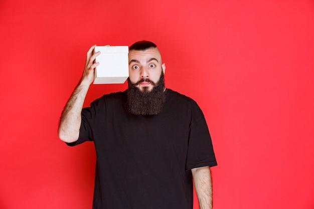 Homem com barba segurando uma caixa de presente branca e parece em dúvida sobre o que há dentro.