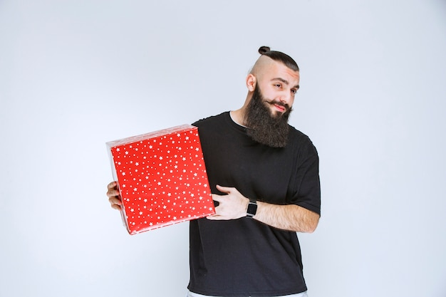 Homem com barba segurando uma caixa de presente vermelha e parece cansado.