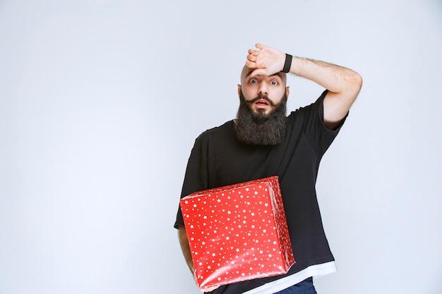 Homem com barba segurando uma caixa de presente vermelha e parece confuso e apavorado.