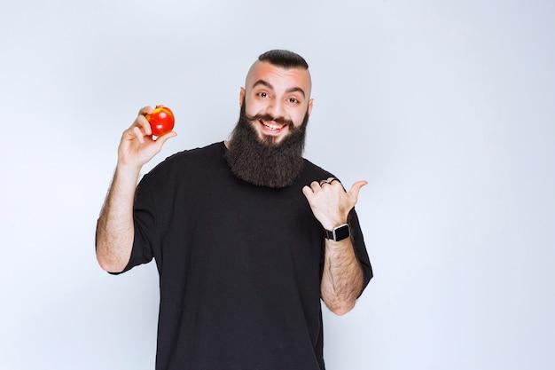 Homem com barba segurando uma maçã vermelha ou pêssego e apreciando o sabor.