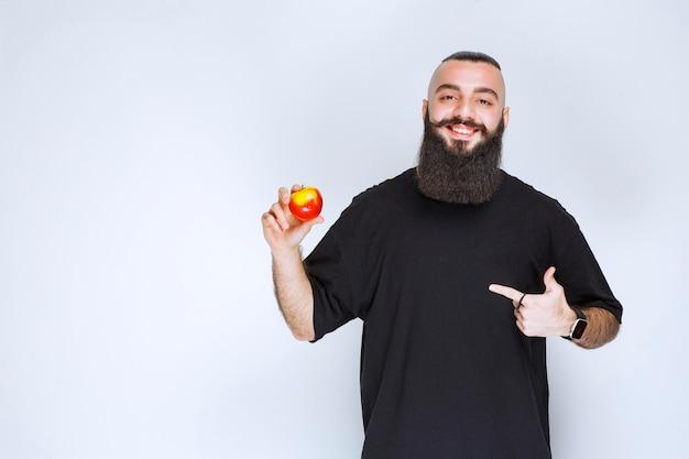 Homem com barba segurando uma maçã vermelha ou pêssego.