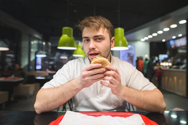 Homem com barba senta-se em um restaurante de fast-food com um hambúrguer nas mãos