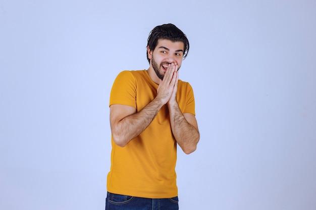Homem com barba unindo as mãos e rezando e pedindo algo