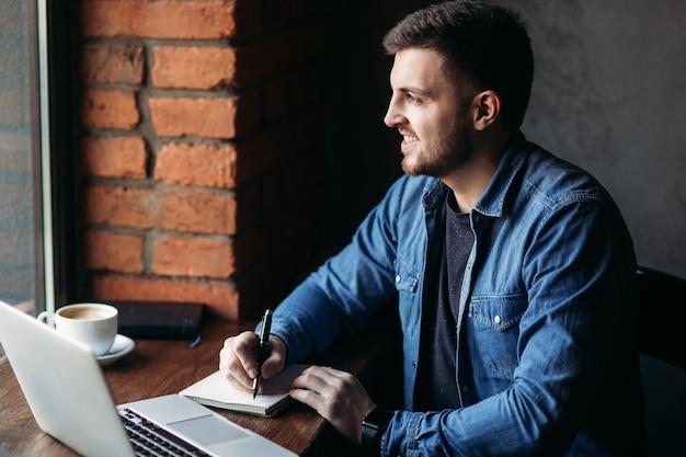 Homem com barba usa um laptop em um café e escreve uma nota.