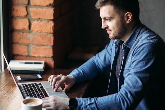 Homem com barba usa um laptop em um café.