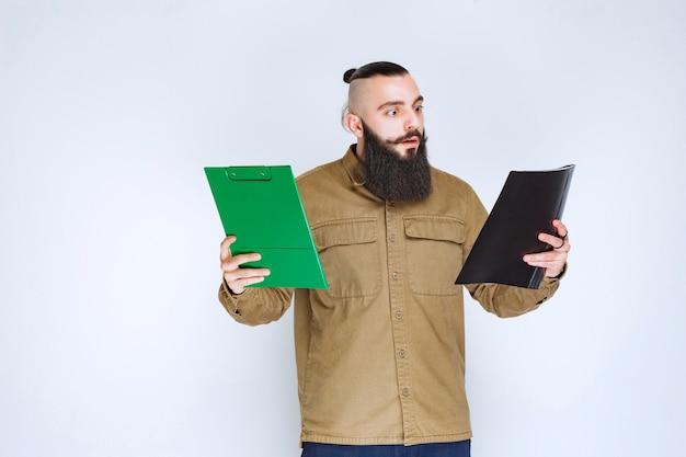 Homem com barba verificando dois projetos diferentes para escolher o vencedor.