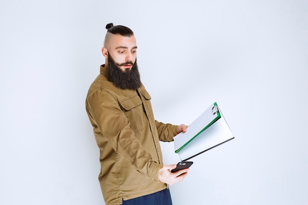 Homem com barba verificando os relatórios contábeis e calculando no telefone.
