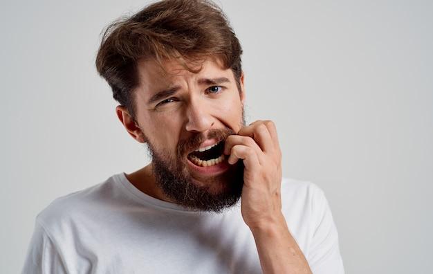 Homem com barba vestindo uma camiseta branca problemas de saúde dores de dente