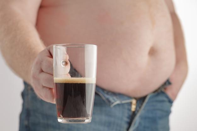 Homem com barriga grande, segurando um copo de refrigerante com gás