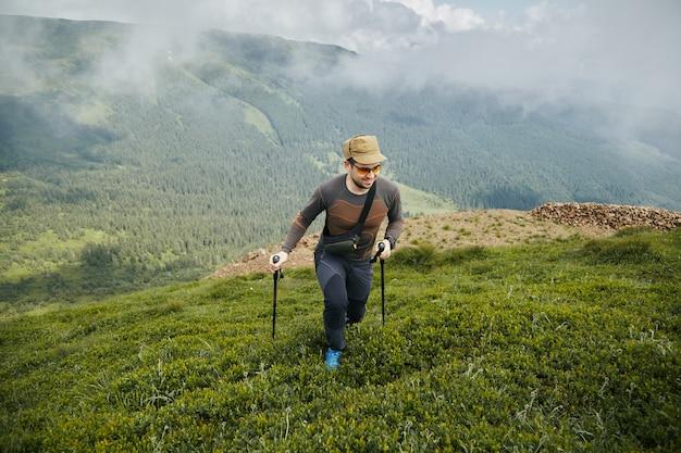 Homem com bastões de trekking e óculos caminhando nas montanhas