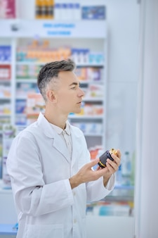 Homem com bata médica com remédio nas mãos