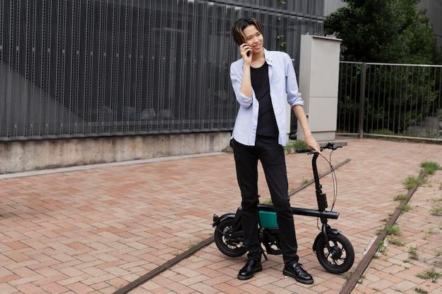 Homem com bicicleta elétrica na cidade falando ao telefone