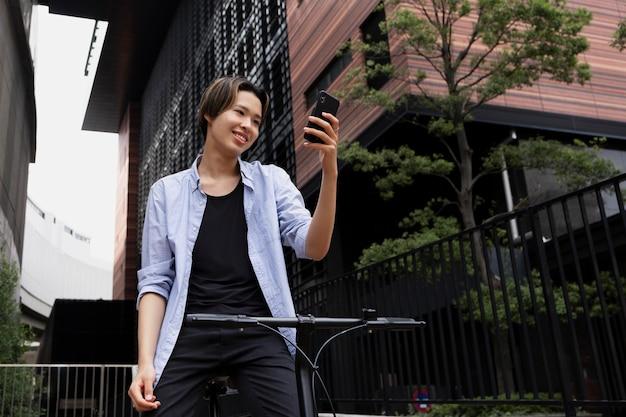Homem com bicicleta elétrica na cidade usando smartphone