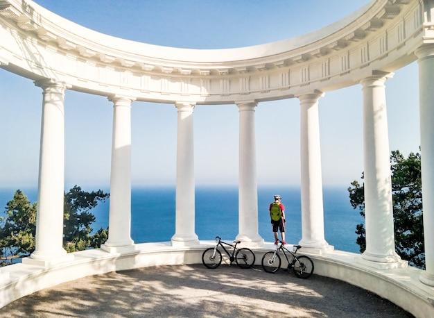 Homem com bicicleta em pé na colunata e olhando para o mar azul