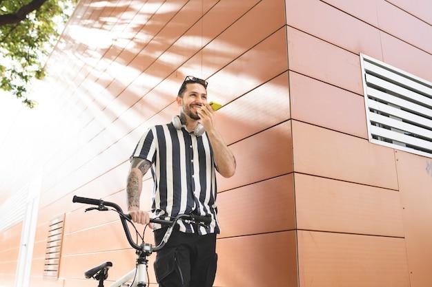 Homem com bicicleta enviando áudio com seu smartphone