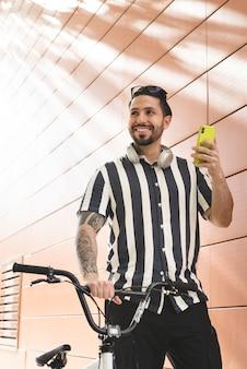 Homem com bicicleta enviando mensagem de áudio com smartphone