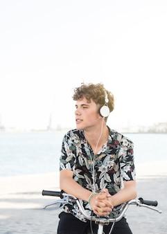 Homem com bicicleta ouvindo música no fone de ouvido ao ar livre