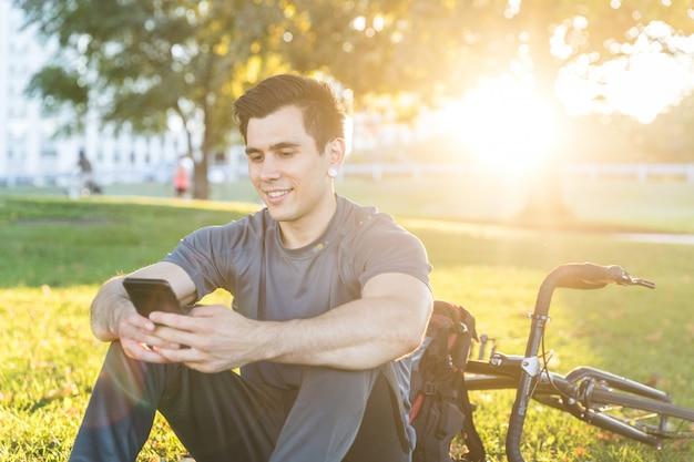 Homem com bicicleta usando telefone no parque ao pôr do sol