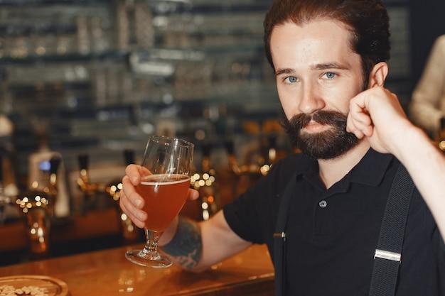 Homem com bigode e barba está no bar e bebe álcool em um copo.