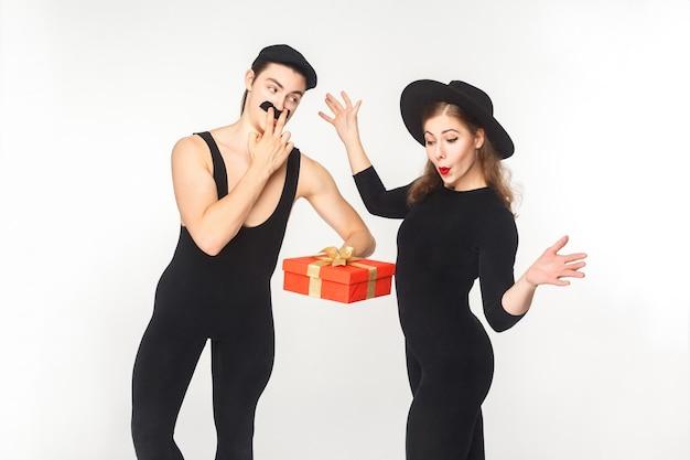 Homem com bigode falso presente caixa de presente mulher chocada. foto do estúdio, isolada no fundo branco