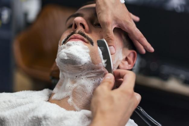 Homem com bigode fazendo a barba