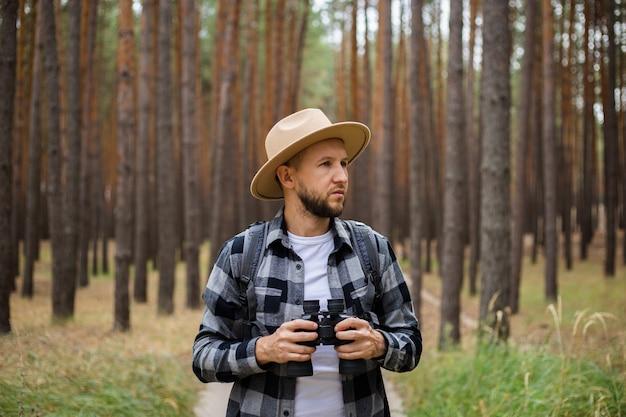 Homem com binóculos na floresta. faça caminhadas nas montanhas ou na floresta.