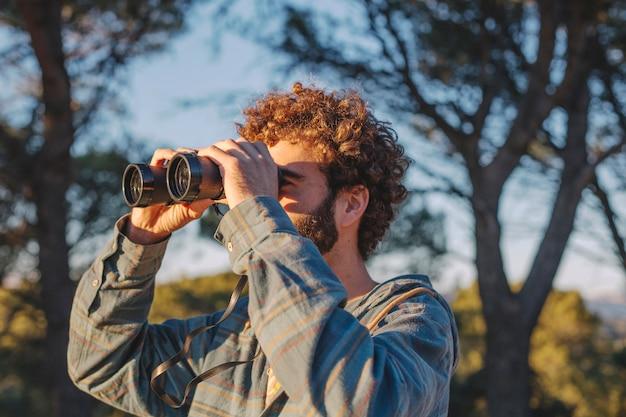 Homem com binóculos na natureza