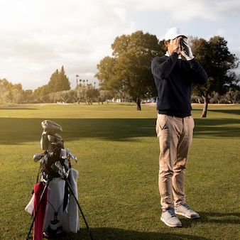 Homem com binóculos no campo de golfe