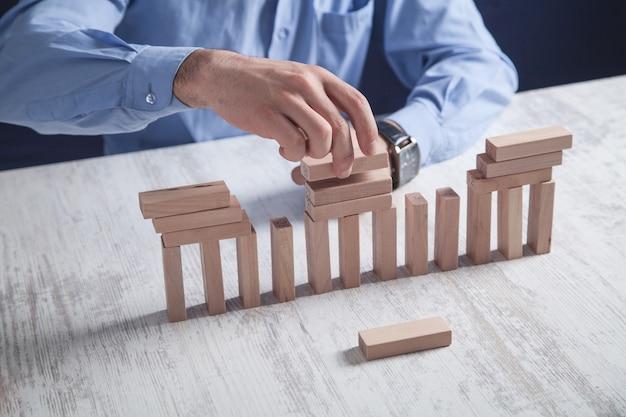 Homem com blocos de madeira. conceito de negócios