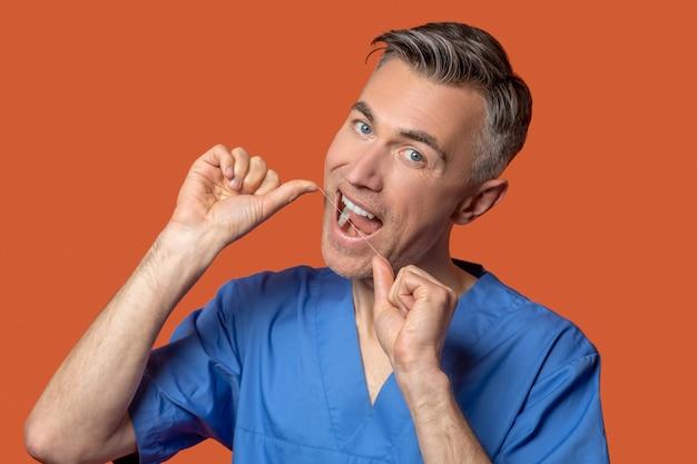 Homem com boca aberta e fio dental